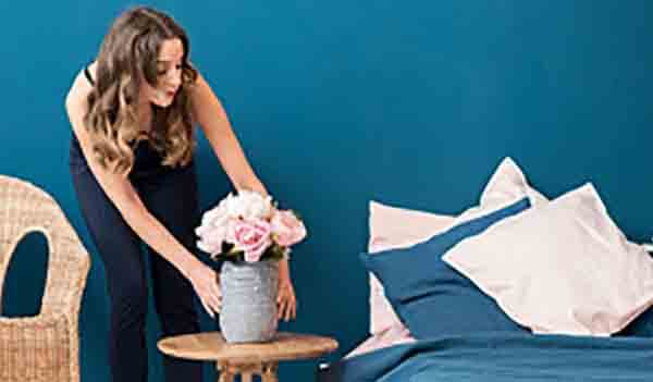 Lady putting a vase of flowers onto a bedside table